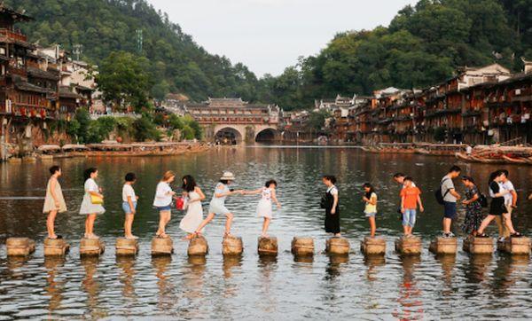 China: Turistas se valen de las piedras para cruzar el rió de Tuojiang - Noticias de hunan